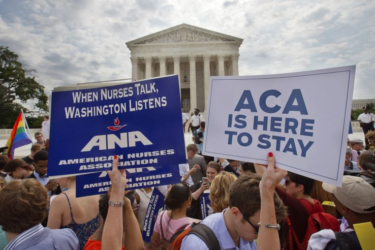 Supporters of the Affordable Care Act hold up signs