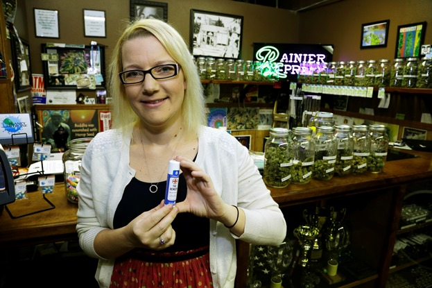Woman holding medical marijuana in pill bottle in dispensary