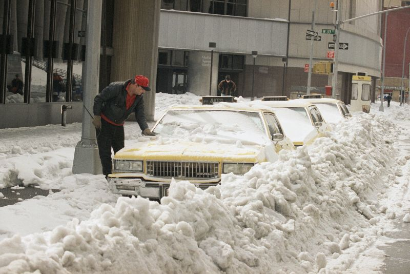 axi driver tries to free his cab from snow