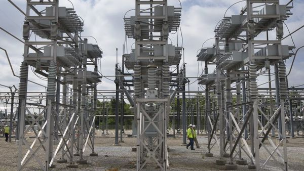 Contractors walk past a capacitor bank at an AEP electrical transmission substation in Westerville, Ohio. (AP Photo/John Minchillo)
