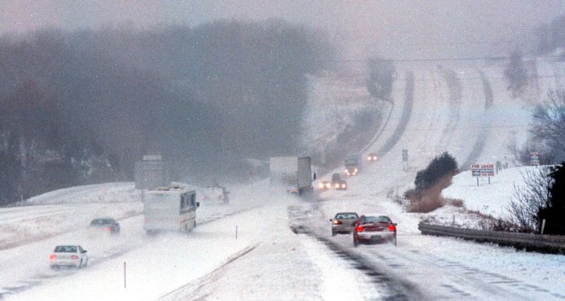 Vehicles attempt to travel on a snow covered I-70 highway near Columbia, Mo. during a snow and ice storm, Friday, Jan. 1, 1999