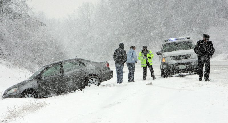 Local police attend to a car that has spun off the road