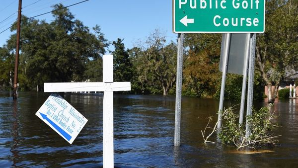 Floodwaters surround road signs on Tuesday, Oct. 11, 2016, in Nichols, S.C. About 150 people were rescued by boats from flooding in the riverside village of Nichols on Monday. (AP Photo/Rainier Ehrhardt)
