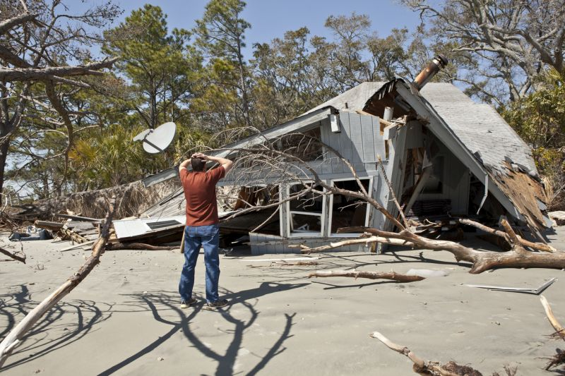 man grieving his destroyed home