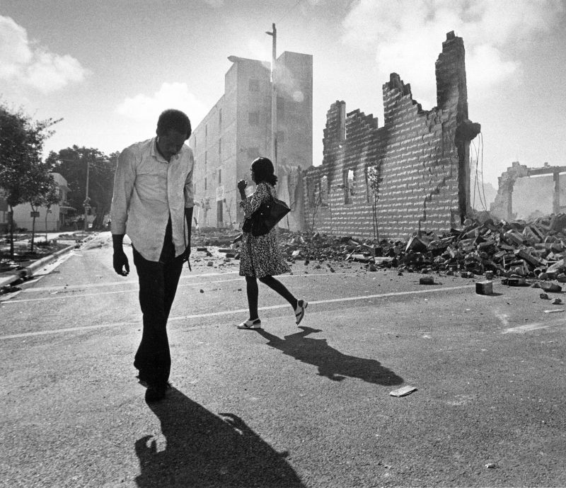 People walk past ruins in the Culmer section of Miami May 19, 1980 after rioting