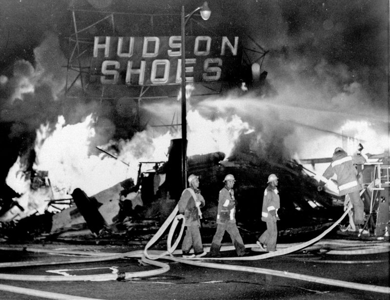 firefighters battle a blaze set in a shoe store during 1965 Watts riots