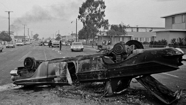 In this Aug. 13, 1965 file photo, the burned-out hulk of an overturned automobile, foreground, and other burned cars at rear block the street at Imperial Highway and Avalon Boulevard during rioting in the Watts district of Los Angeles. (AP Photo/Harold Filan, File)