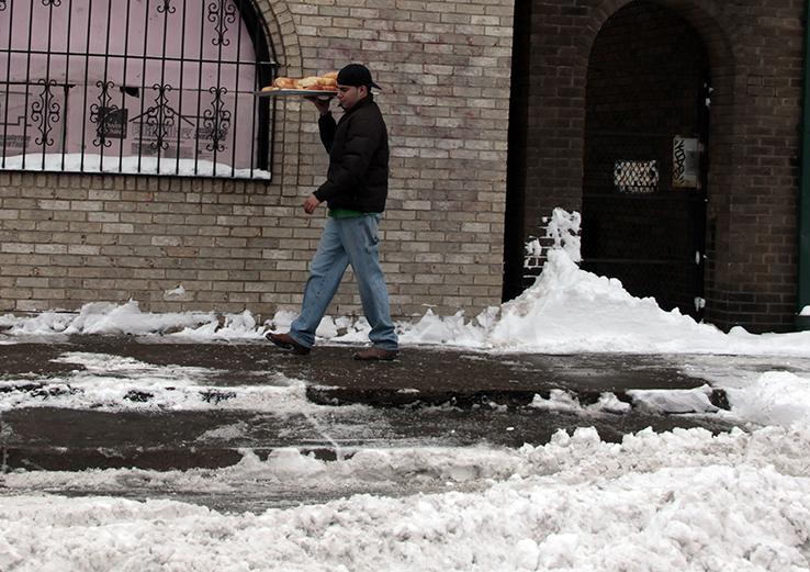 Man delivering bread walking on icy sidewalk