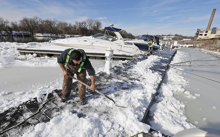 Man shoveling snow off dock on James River, VA