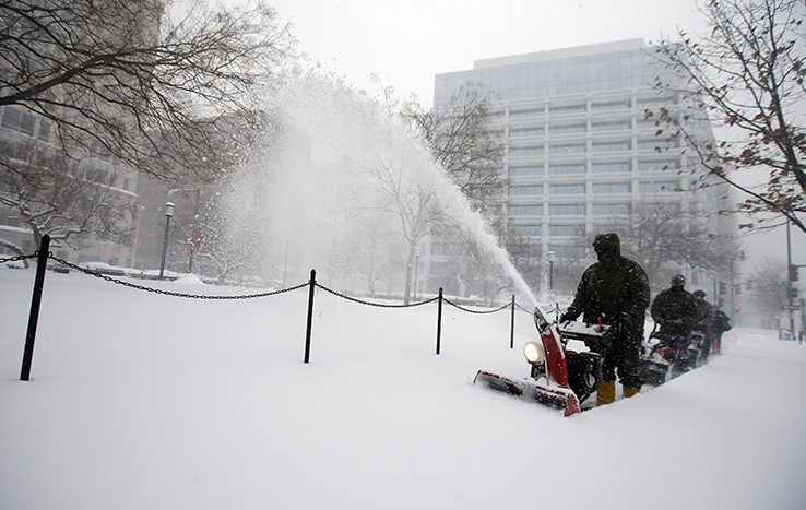 US Park Service employees clean snow off sidewalk with snow blower