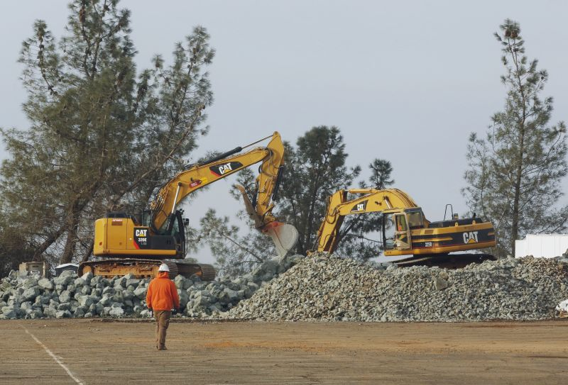 Construction equipment moves piles of rock at a staging area near the Oroville Dam