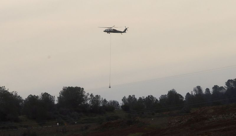 A helicopter lowers a bag of rocks to be dropped on a hole on the lip of the Oroville Dam's emergency spillway