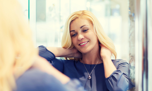 Blonde woman trying on necklace looking in mirror