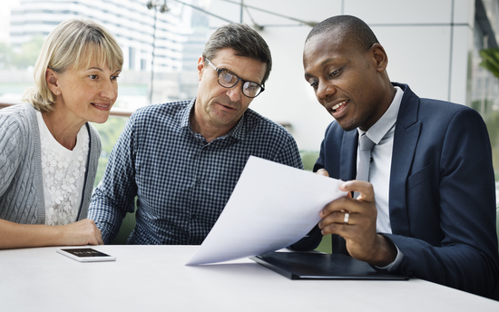 Mature couple meeting with young African American insurance agent advisor