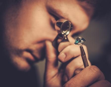 Man looking at gem through loup