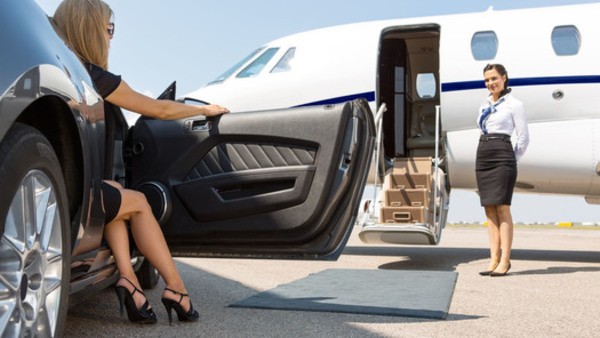 A high net worth client is greeted by a flight attendant before boarding her private jet. (Source: Shutterstock)