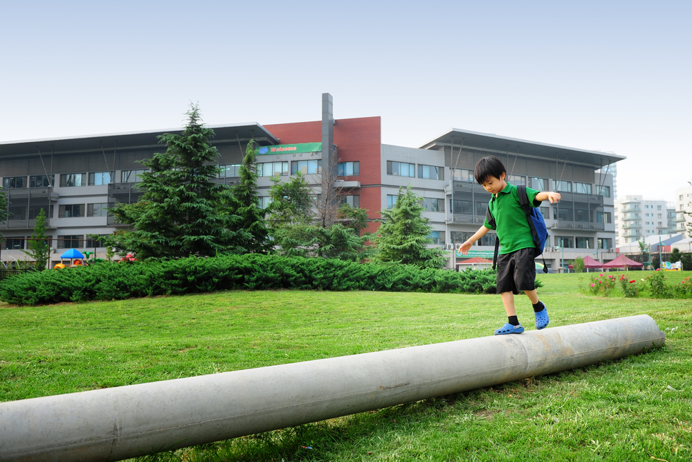little boy running on a pipe in front of a school