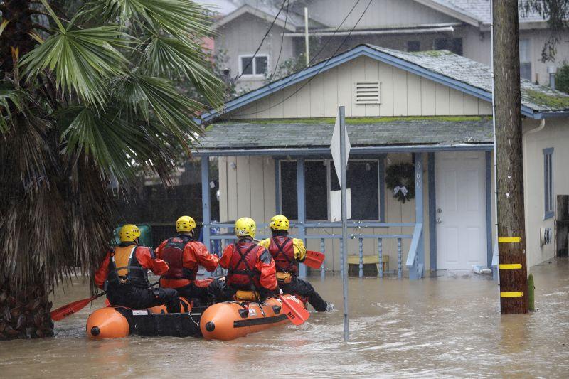 Rescue crews survey a flooded neighborhood