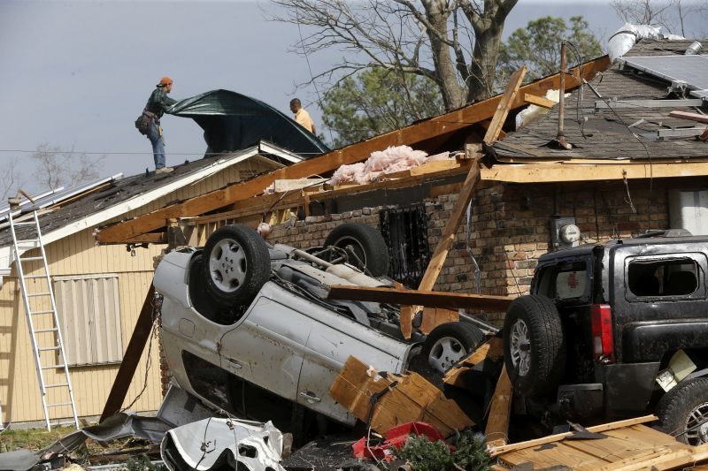 Workers put a tarp on the roof of a damaged home in the aftermath of a tornado that tore through New Orleans East