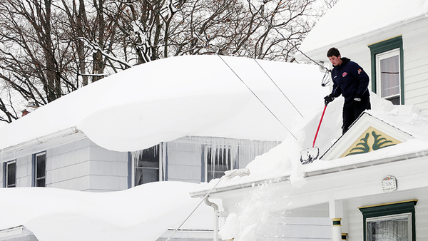 Andrew Zelak cleans the snow from his roof on Irving Place in Alden, N.Y., Nov. 20, 2014. The weight of the snow has caused problems around the area with roofs collapsing and structures fracturing. (Photo: AP/Gary Wiepert)