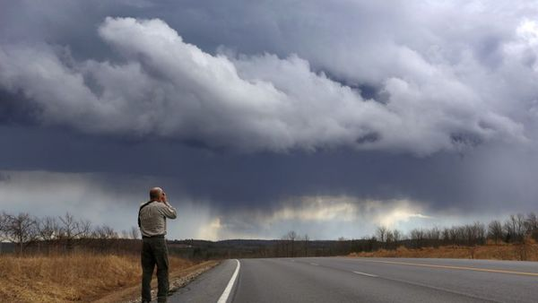 Jonathan Rundell, of Scarborough, Maine, photographs storm clouds moving through New Gloucester, Maine, Thursday, March 17, 2016. Randell pulled off Rt. 26 to record the scene after a thunder and hail storm moved through the region. (AP Photo/Robert F. Bukaty)
