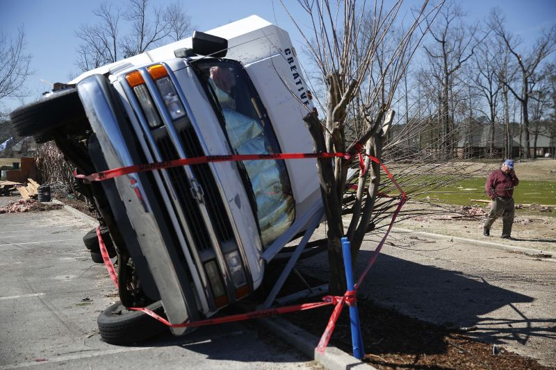 Owner of a truck overturned by a tornado, talks on the phone with insurance agents