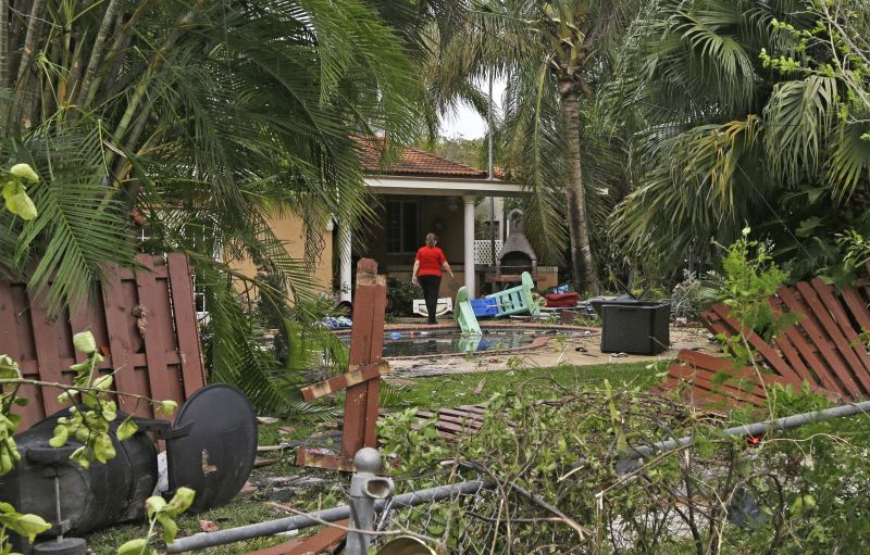 A woman walks through her backyard covered by debris caused by severe weather