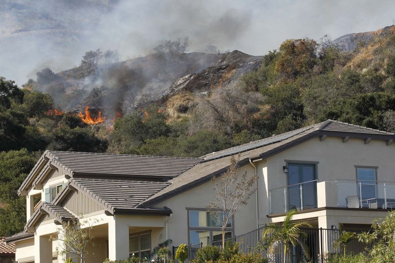 A wildfire burns next to homes built near a hilltop in Azusa, Calif.