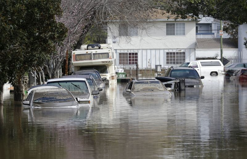 Submerged automobiles are shown on flooded Nordale Avenue in San Jose, Calif