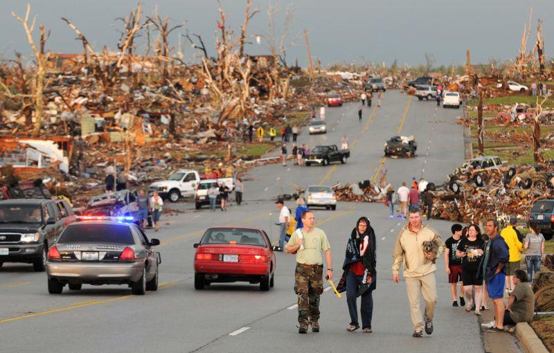 residents walk in the street after a massive tornado hit Joplin, Mo.