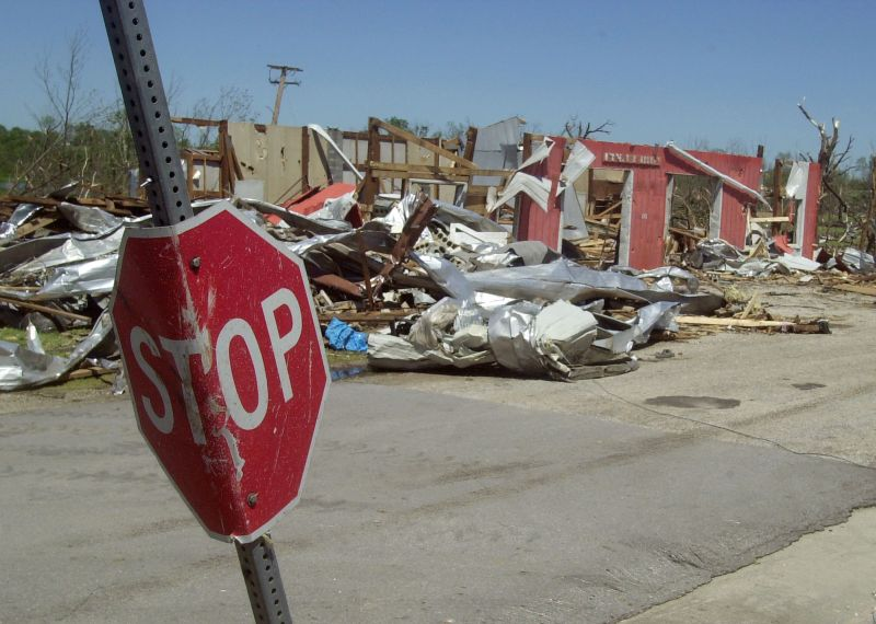 A stop sign is wrapped around a post with tornado damage and debris in the background in Stockton, Mo.
