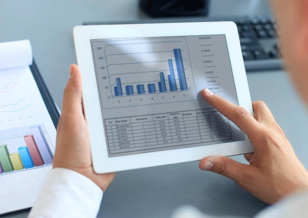 man on iPad looking at financial data