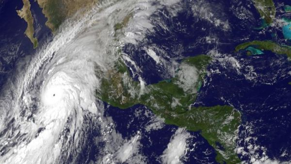 This satellite image released by the National Oceanic and Atmospheric Administration shows Hurricane Patricia, left, moving over Mexico's Pacific Coast on Oct. 23, 2015. (NOAA via AP)