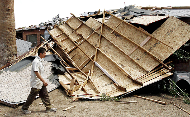 Man looking at damage to his property from sand storm in Arizona