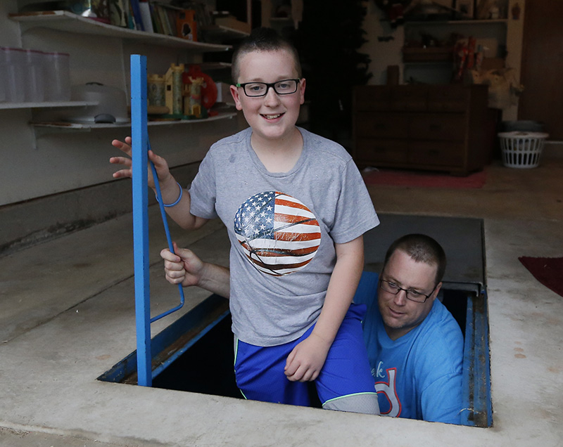 Family emerging from storm shelter in basement of home