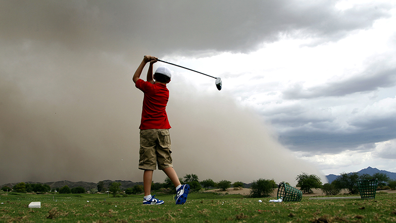 Young man on driving range in sand storm in Arizona