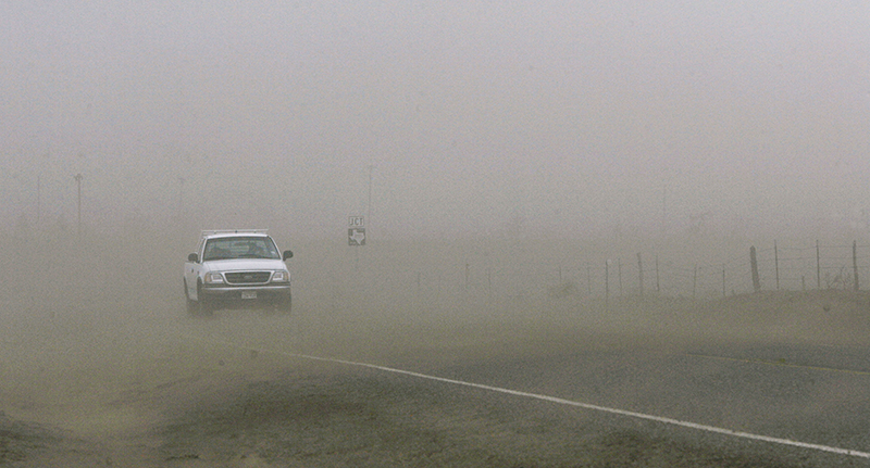 White pick up truck driving in Texas dust storm