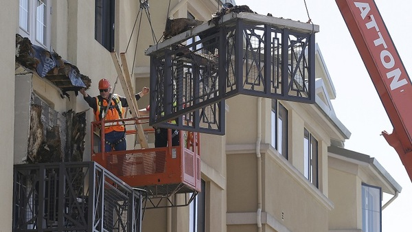 In this photo, workers remove debris from a fatal balcony collapse in 2015 at the Library Gardens apartment complex in Berkeley, California. (Associated Press file photo/Jeff Chiu)