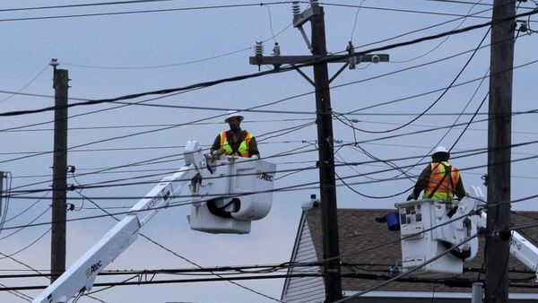Utility crews work on power lines in response to superstorm Sandy as dusk falls in Ship Bottom, a community on Long Beach Island, N.J., Thursday, Nov. 1, 2012. (AP Photo/Patrick Semansky)