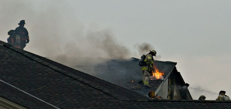 Firefighters work on the roof of a structure which was apparently struck by lightning setting