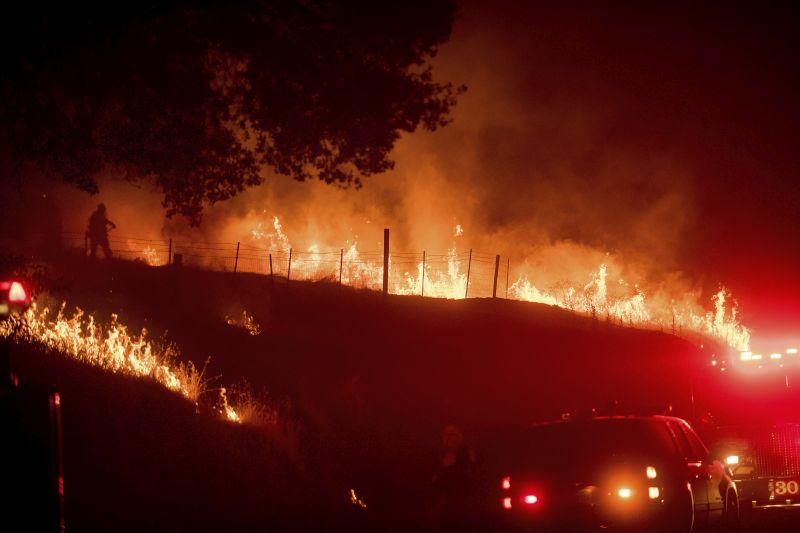 Flames from a backfire burn as CalFire crews battle a wildfire near Mariposa, Calif.