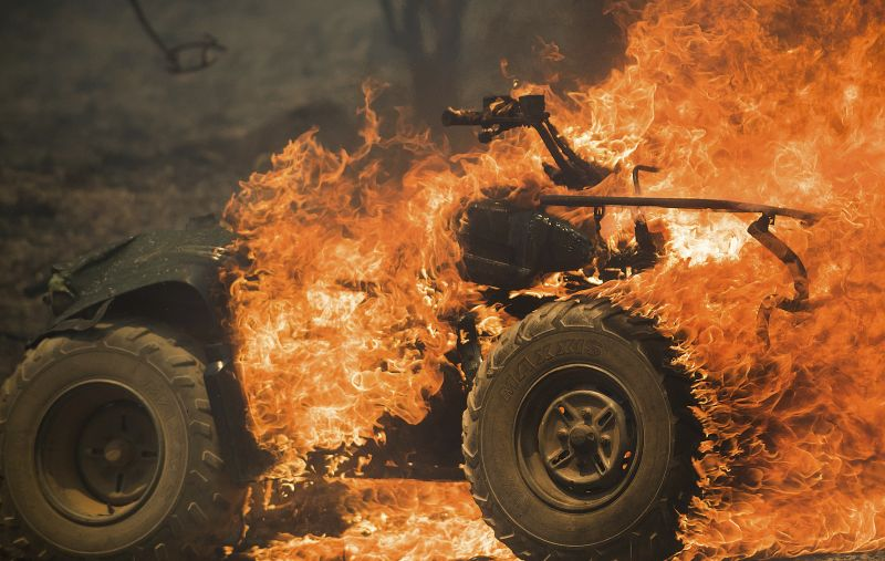 Flames from a wildfire consume an all-terrain vehicle near Oroville, Calif.
