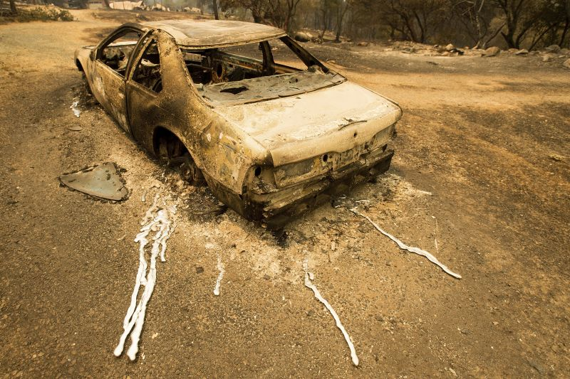 scorched car rests next to a residence leveled by the Detwiler fire near Mariposa, Calif.