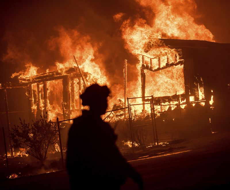 Flames from a wildfire consume a residence near Oroville, Calif.