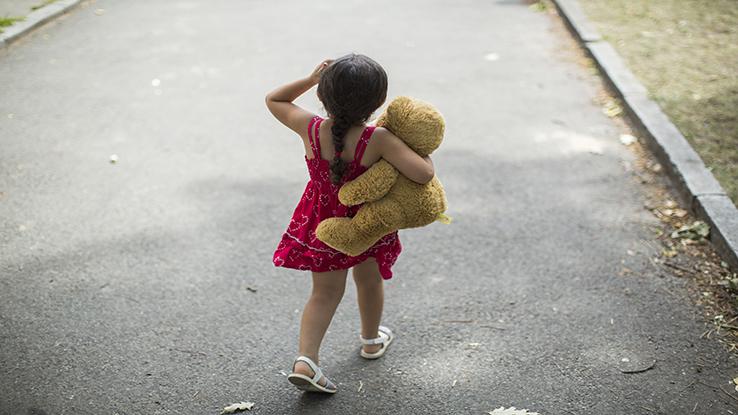 Back of little girl holding teddy bear