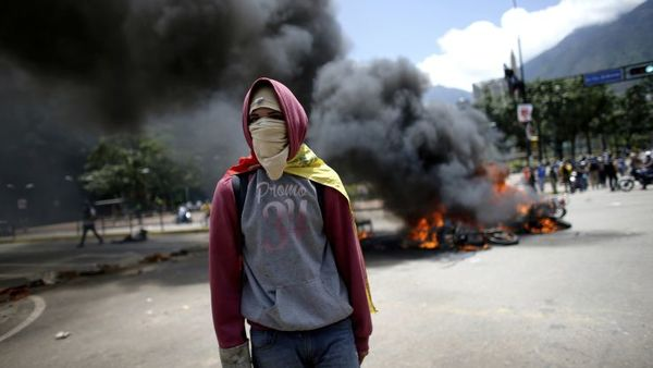 A demonstrators walks near a pile of privately owned motorcycles burned by the police after an explosion at Altamira square during clashes with anti-government demonstrators in Caracas, Venezuela, Sunday, July 30, 2017. (AP Photo/Ariana Cubillos)