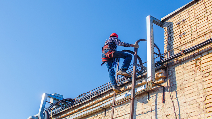 Man climbing onto roof with fall protection