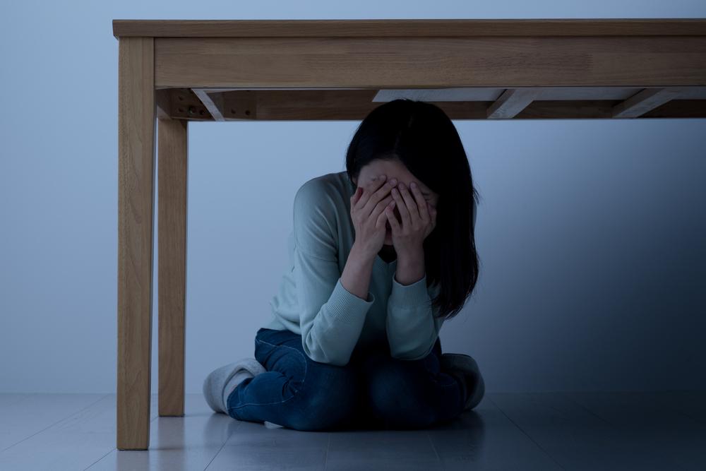 woman hiding under a table
