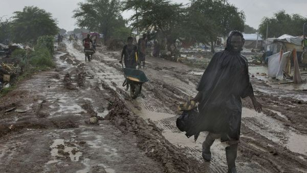 People trudge along the road during wet season in South Sudan. (AP Photo/ Matthew Abbott)