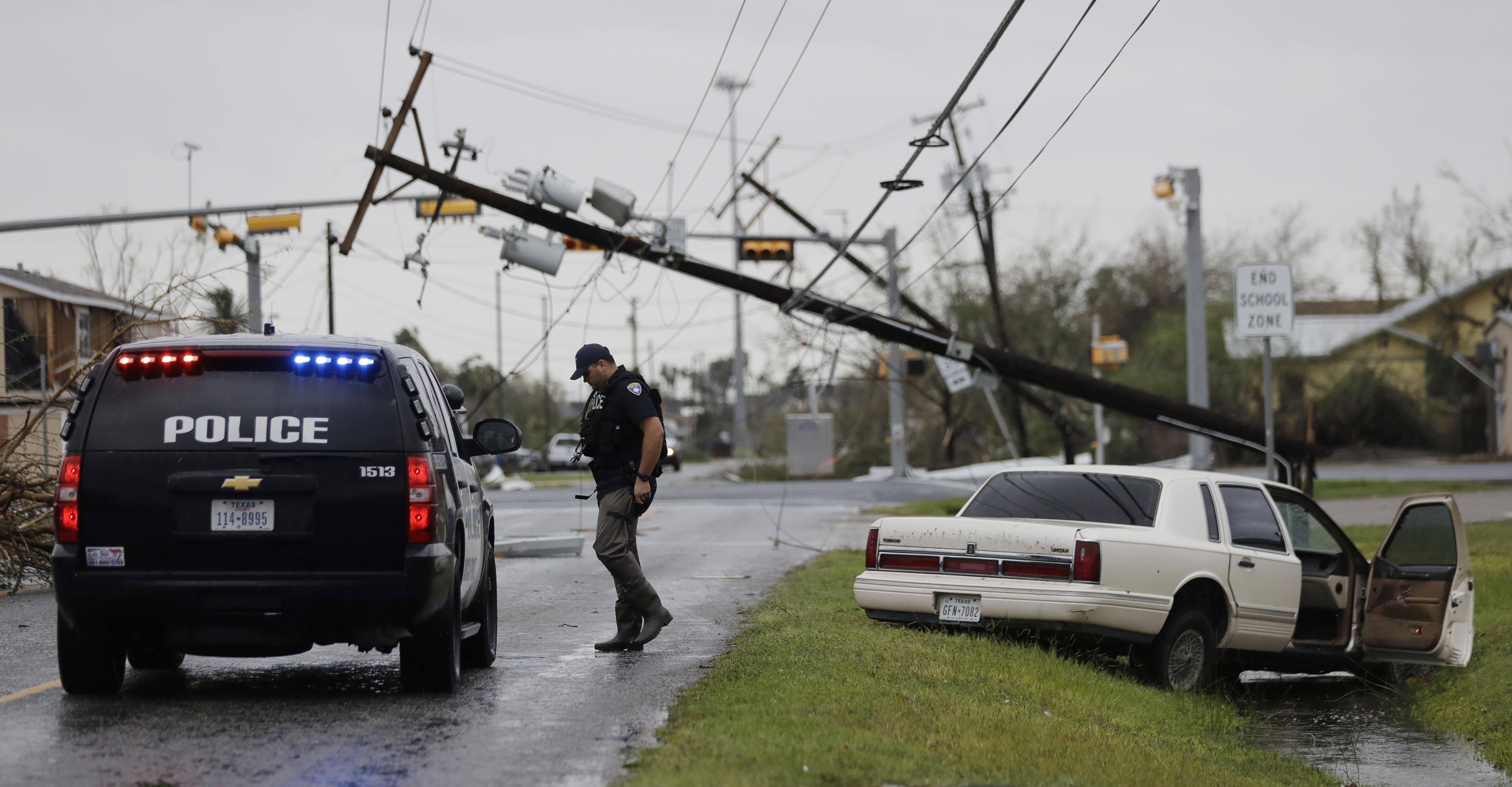 Police officer checks abandoned cars during Hurricane Harvey